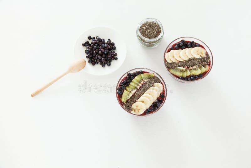 Due piatti dei frullati della bacca con i mirtilli, banana e kiwi e semi di chia su un fondo bianco fotografie stock