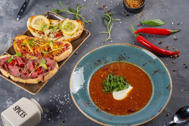 Due piatti di minestra deliziosa con il servizio di Bruschette immagine stock