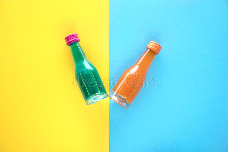 Due piccole bottiglie di vetro con un cocktail blu ed arancio su un fondo blu e giallo Due di piccole bottiglie colorate multi co immagini stock