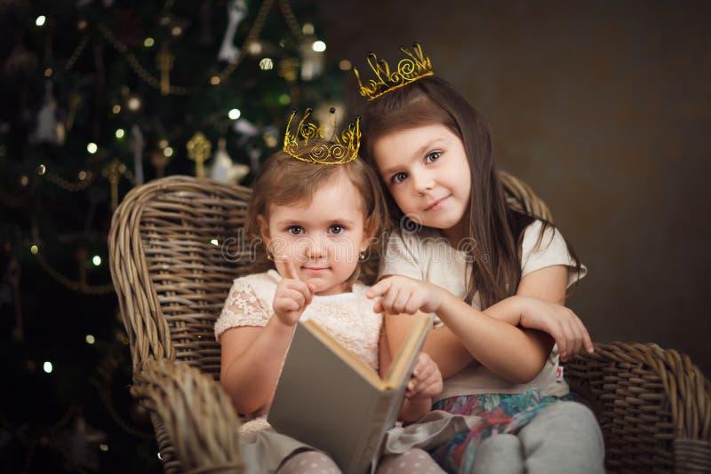 Due piccole ragazze sveglie che si siedono vicino all'albero di Natale e che leggono la BO immagine stock