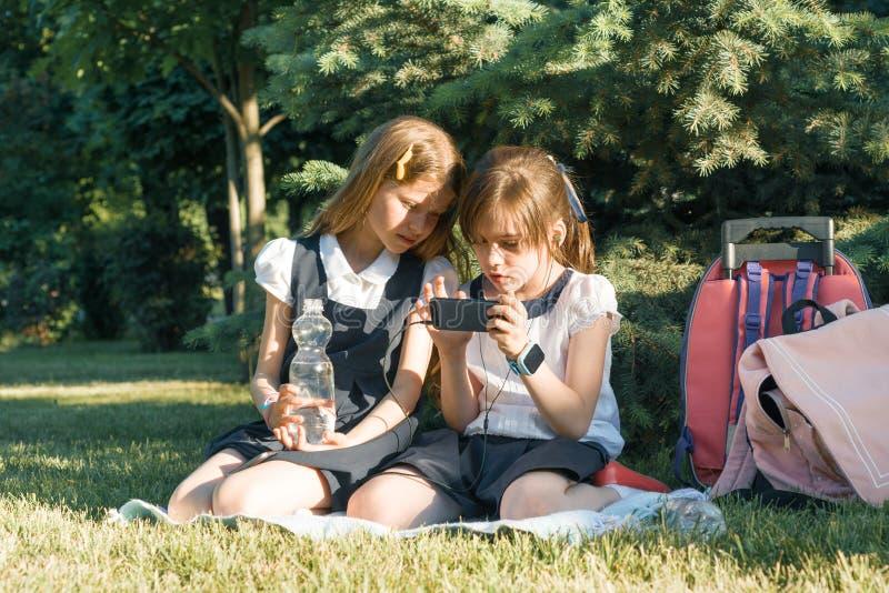 Due piccole scolare che per mezzo di uno smartphone Bambini che giocano, lettura, esaminante il telefono, nel parco, ora dorata L fotografia stock