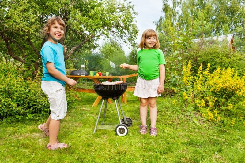 Due piccole sorelle che stanno BBQ vicino e grigliare immagini stock