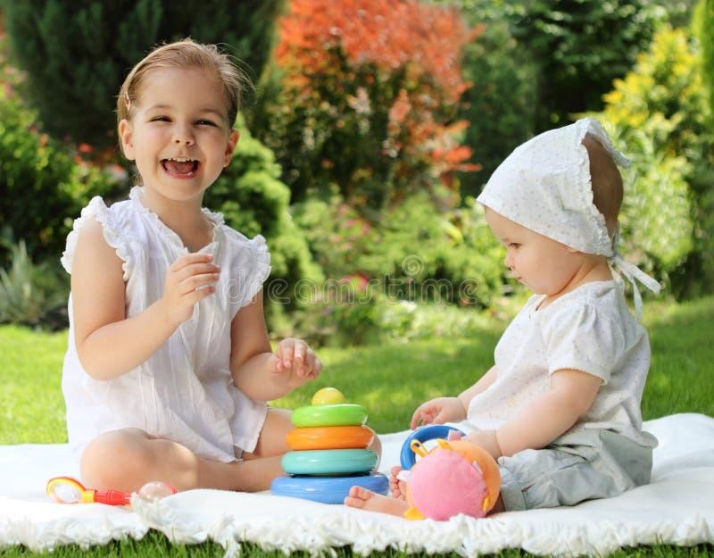 Due piccole sorelle nel giardino di estate fotografia stock libera da diritti