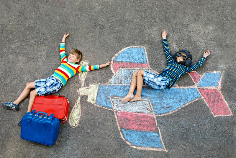 Due piccoli bambini, ragazzi dei bambini divertendosi con con il disegno dell'immagine dell'aeroplano con i gessi variopinti su a fotografie stock libere da diritti