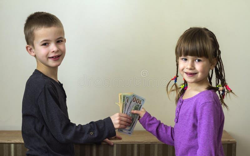 Due piccoli bambini ragazzo e ragazza che giocano con i soldi dei dollari fotografia stock
