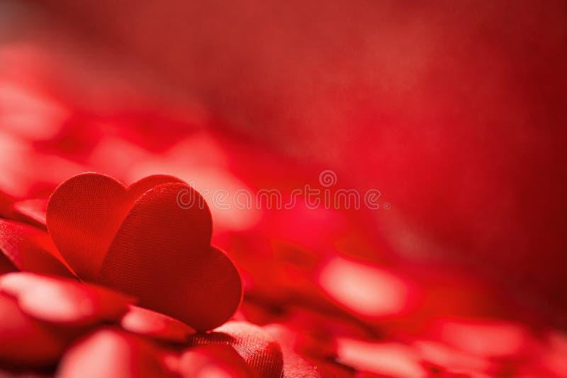 Due piccoli cuori rossi del raso su fondo rosso, giorno di biglietti di S. Valentino o amore di celebrazione immagine stock