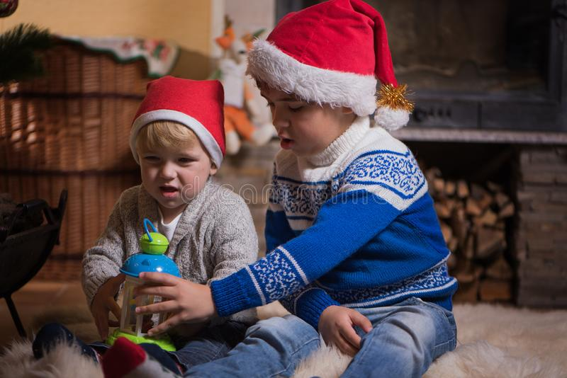 Due piccoli fratelli germani in cappelli di Santa che giocano vicino al camino fotografie stock