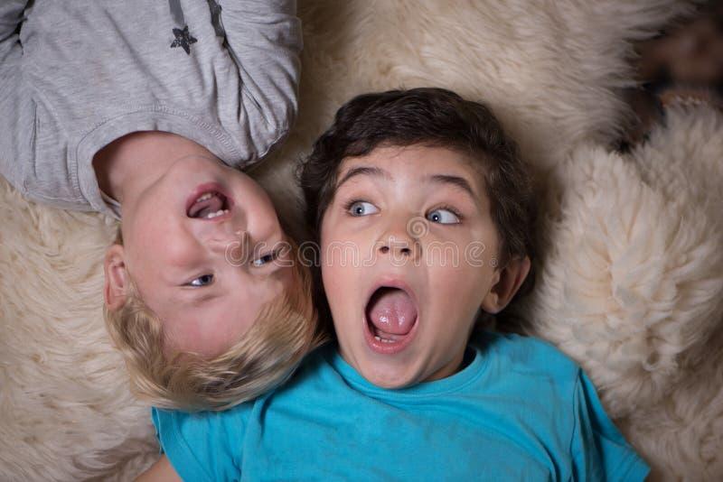 Due piccoli fratelli impertinenti che si trovano sulla pelliccia lanuginosa e che gridano fotografie stock