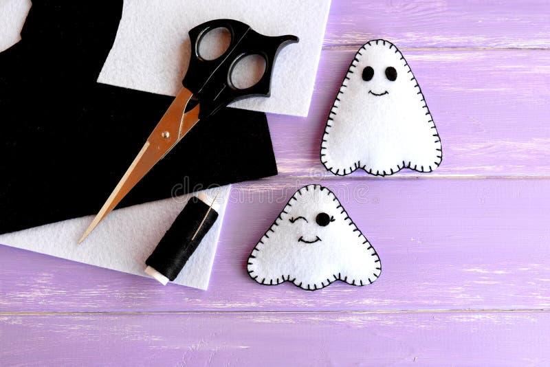 Due piccoli mestieri bianchi dei fantasmi, feltro riveste, forbici, il filo, ago su fondo di legno lilla Idea della decorazione d immagine stock