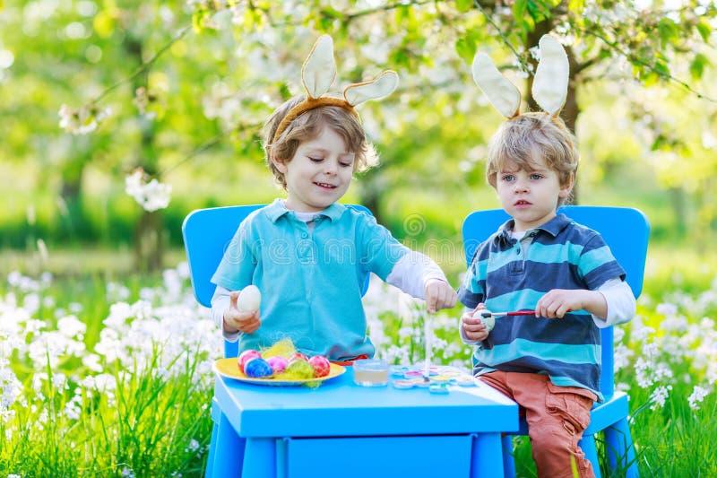 Due piccoli ragazzi gemellati in orecchie del coniglietto di pasqua che colorano le uova fotografia stock libera da diritti