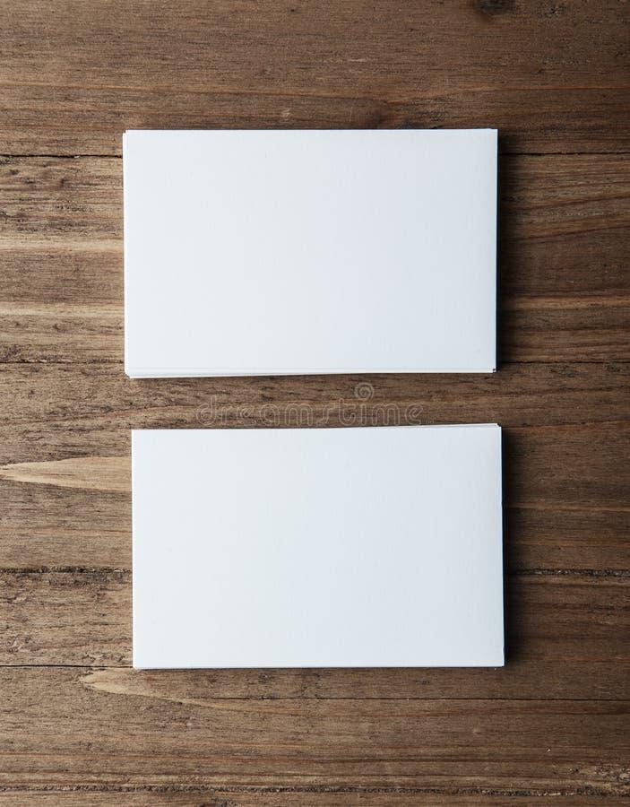 Due pile di biglietti da visita bianchi in bianco sul verticale di legno del fondo fotografia stock