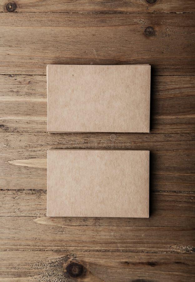 Due pile di carte di impresa artigiana in bianco sul verticale di legno del fondo fotografia stock