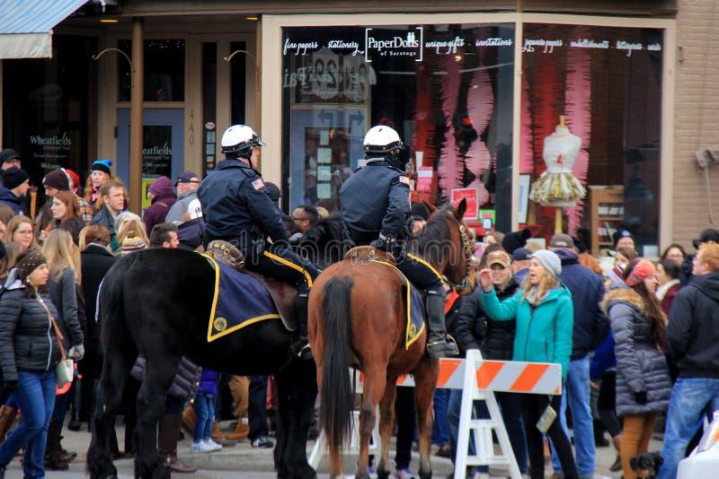Due polizie sui cavalli, tenenti ammucchiano nel controllo durante il Chowderfest, Saratoga Springs, New York, 2016 fotografie stock libere da diritti