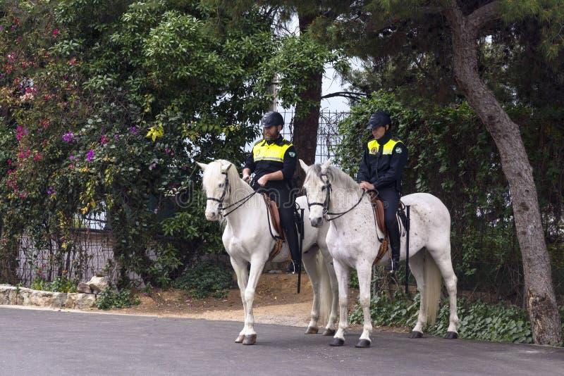 Due poliziotti a cavallo sorvegliano l'area del parco vicino alla fortezza di Gibralfaro fotografia stock libera da diritti