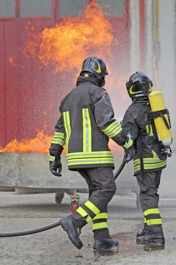 DUE pompieri con le bombole d'ossigeno fuori dal fuoco fotografia stock libera da diritti
