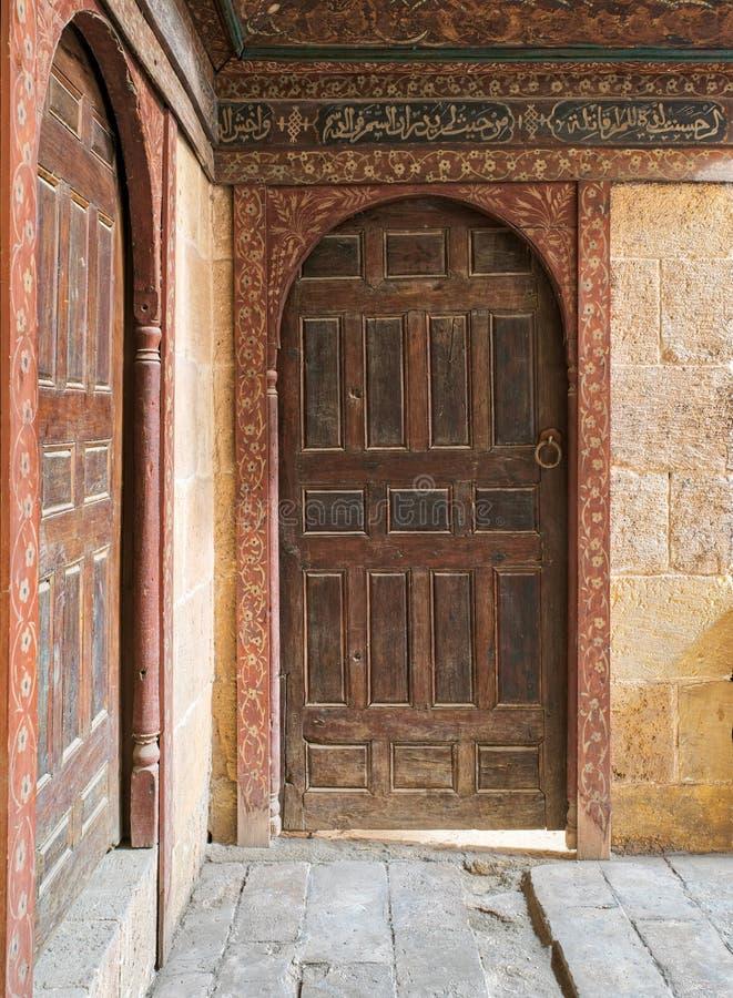 Due porte perpendicolari arcate decorate invecchiate di legno sulle pareti di mattoni di pietra immagini stock libere da diritti