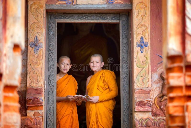Due principianti stanno stando insieme i libri di lettura nel tempio immagine stock libera da diritti