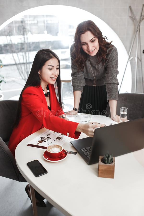 Due progettisti delle ragazze stanno lavorando con il computer portatile e la documentazione al progetto nell'ufficio alla moda C fotografia stock libera da diritti