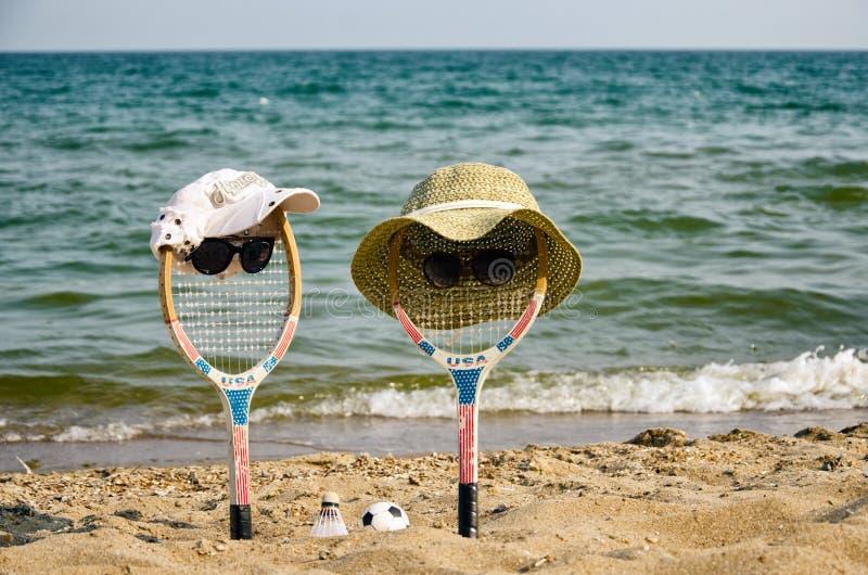Due racchette (boy&girl) riposano sulla spiaggia immagini stock libere da diritti