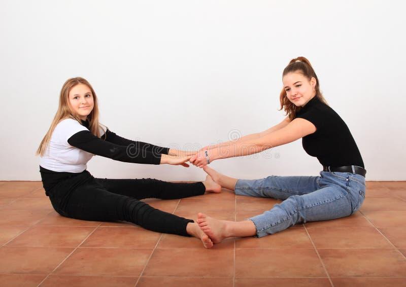 Due ragazze adolescenti che si allungano immagine stock