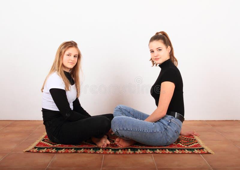 Due ragazze adolescenti sedute su tappeto orientale fotografia stock