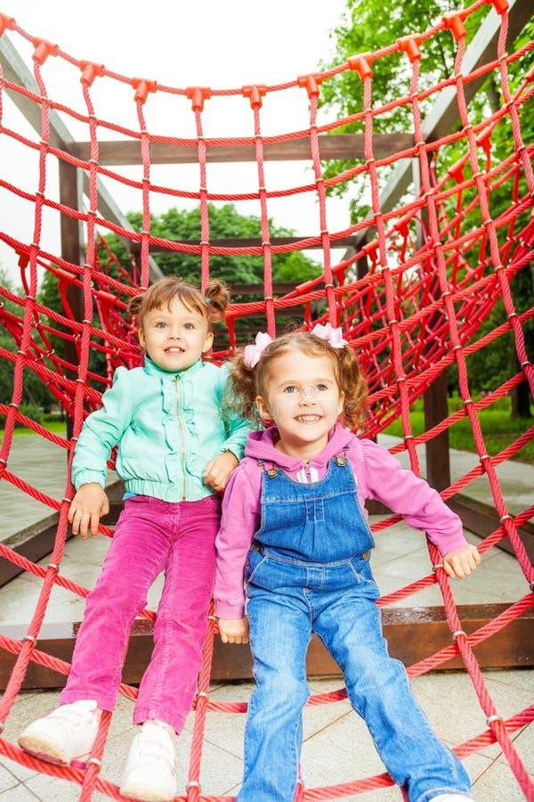 Due ragazze affascinanti su rete del campo da giuoco fotografie stock