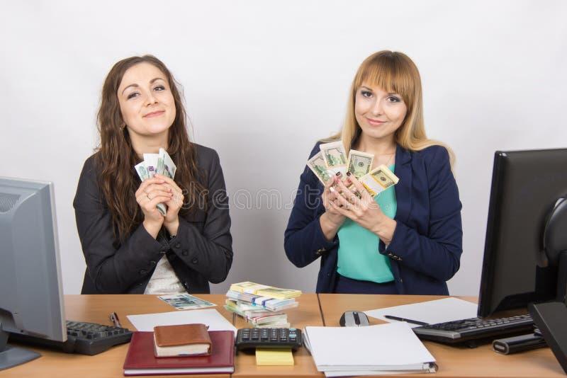 Due ragazze ai soldi dell'abbraccio dell'ufficio dello scrittorio imballa fotografie stock libere da diritti