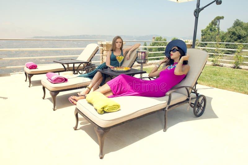 Due ragazze alla moda che si siedono sulle sedie di spiaggia che godono del tempo tropicale fotografia stock libera da diritti