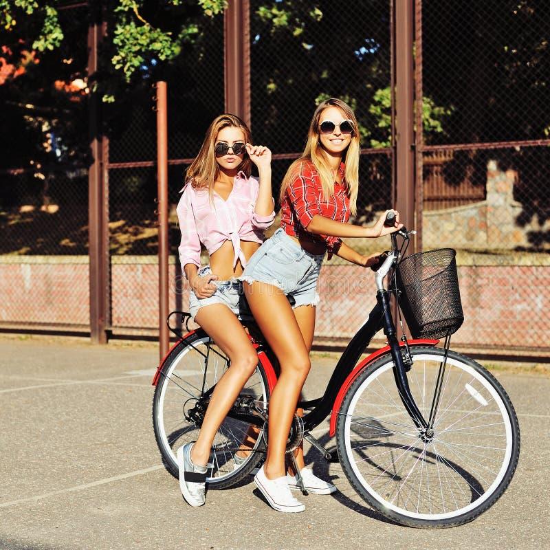 Due ragazze alla moda su una bicicletta nell'estate immagini stock libere da diritti