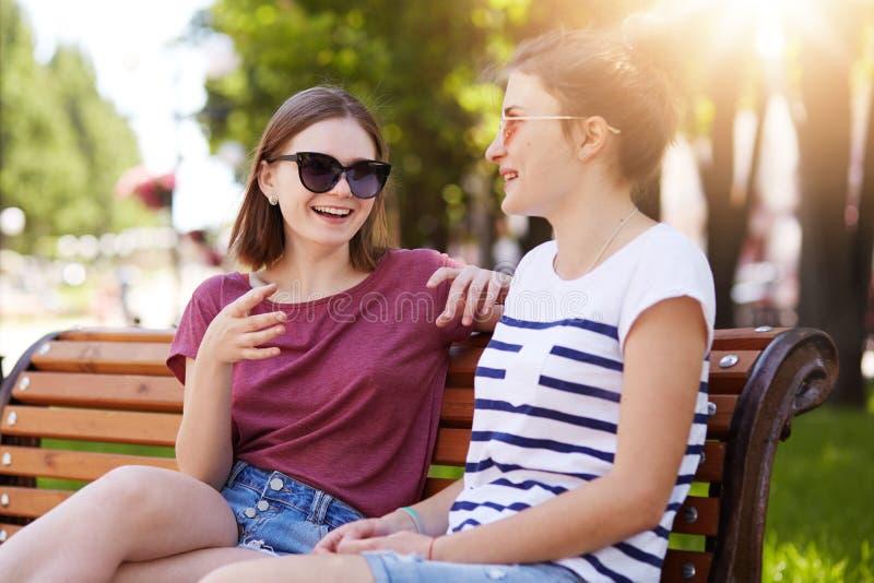 Due ragazze allegre si rilassano insieme in parco locale che si siede sul nuovo banco di legno, fanno gli scherzi, gossip, ricord immagine stock