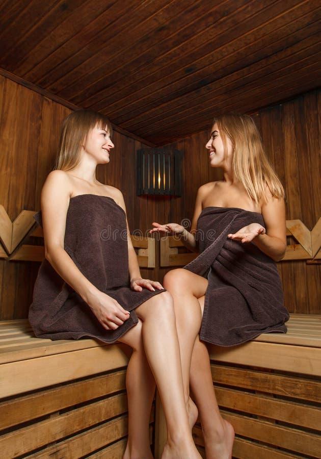 Due ragazze in asciugamani nella sauna fotografie stock