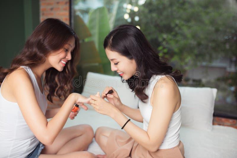 Due ragazze asiatiche che dipingono le unghie del piede e le unghie su un letto in Li immagine stock
