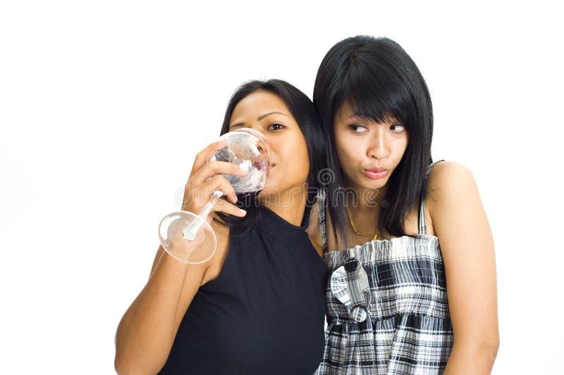 due ragazze asiatiche con vino rosso immagine stock libera da diritti