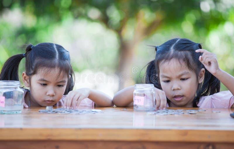Due ragazze asiatiche del bambino che contano e che mettono moneta nella bottiglia fotografia stock libera da diritti