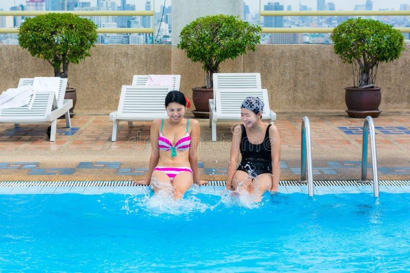 Due ragazze asiatiche stanno spruzzando l'acqua sulla piscina fotografia stock
