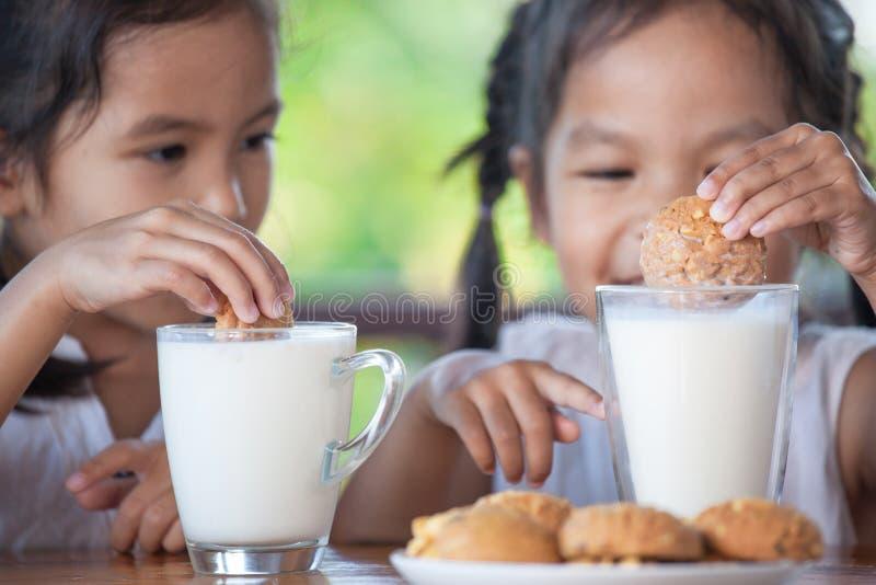 Due ragazze asiatiche sveglie del piccolo bambino stanno mangiando i biscotti con latte immagini stock