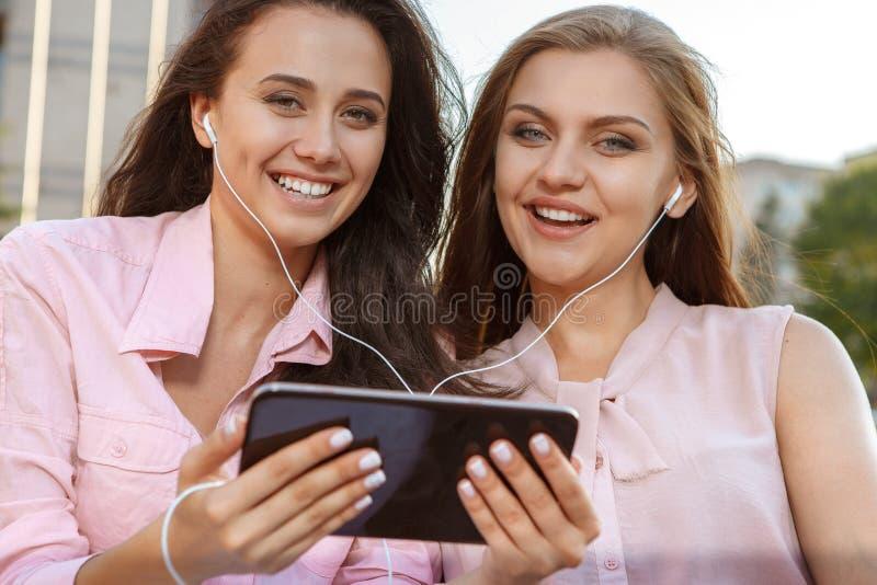 Due ragazze attraenti che ascoltano la musica fotografia stock