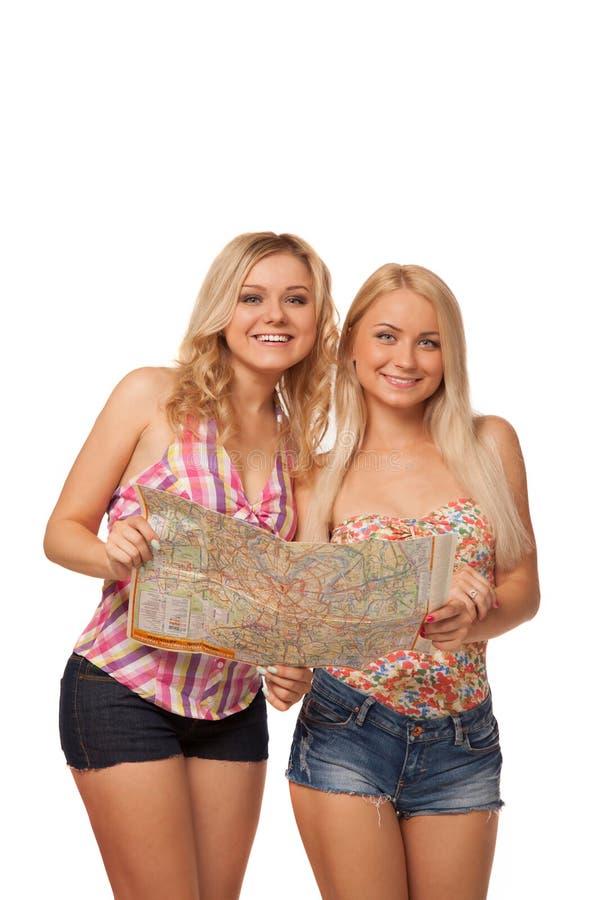 Due ragazze bionde che indossano gli shorts dei jeans con la mappa fotografia stock