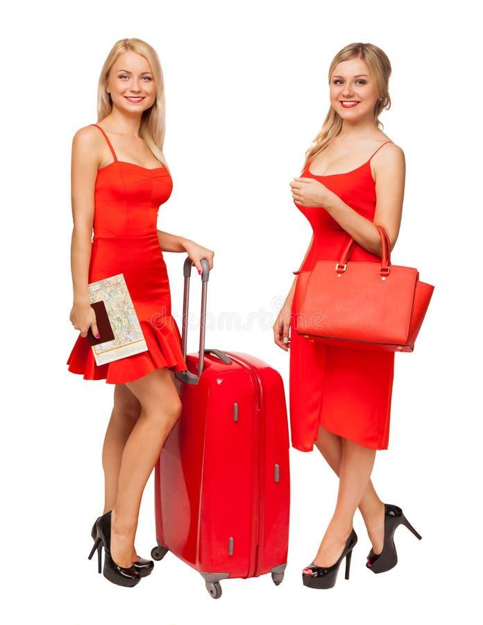 Due ragazze bionde che indossano il rosso si veste con la grandi valigia e borsa immagini stock