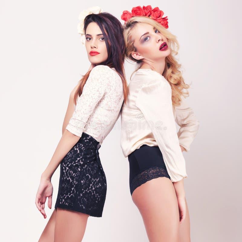 Due ragazze calde integrali su fondo grigio fotografia stock