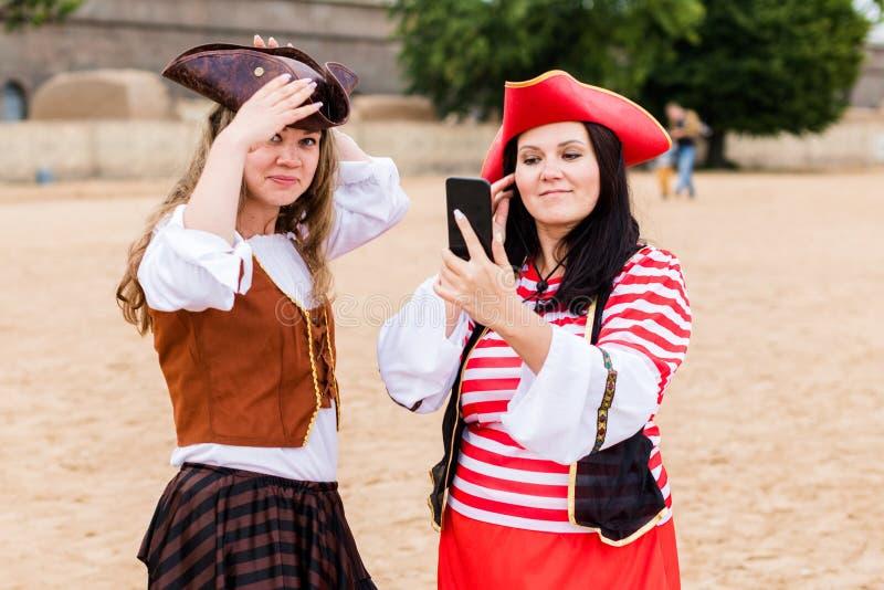 Due ragazze caucasiche felici e sorridenti, vestite da pirati, preparate con lo smartphone Backstage immagini stock