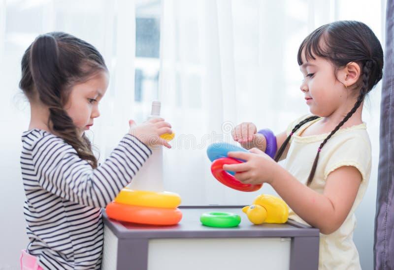 Due ragazze caucasiche sveglie che giocano insieme i giocattoli nella casa Sviluppo dei bambini e concetto di svago Casa dolce ca fotografia stock