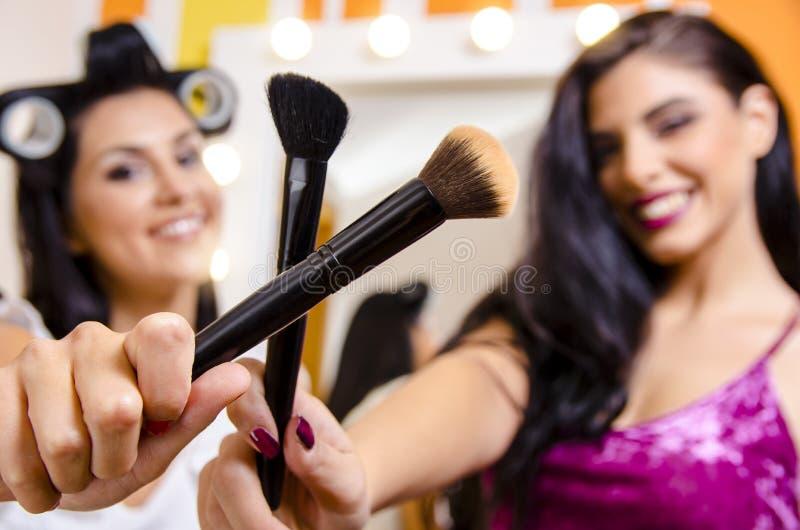 Due ragazze che attraversano le spazzole di trucco, truccatore fotografie stock