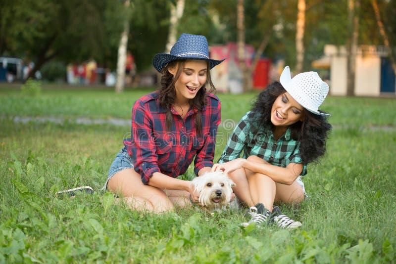 Due ragazze che camminano con il suo cane cappello da cowboy e fotografia stock libera da diritti