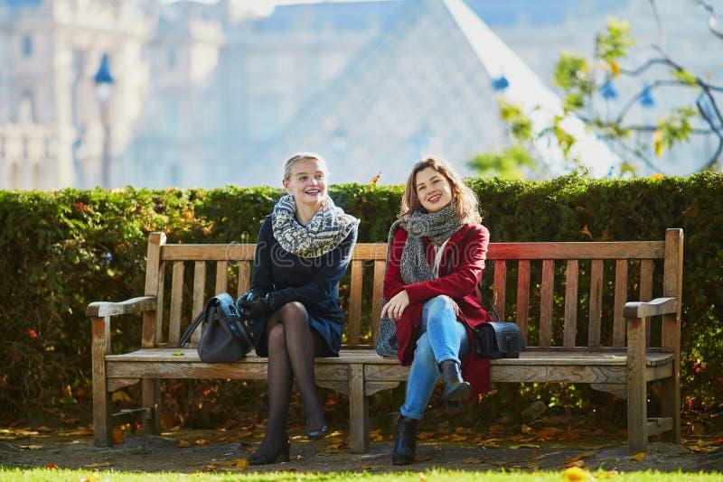 Due ragazze che camminano insieme a Parigi fotografia stock