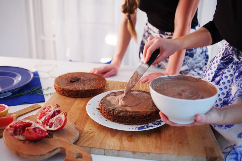 Due ragazze che fanno un dolce sulla cucina Le mani delle donne, causanti la crema del cioccolato fotografie stock libere da diritti