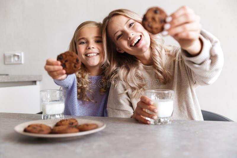 Due ragazze che felici le sorelle alla cucina all'interno mangiano hanno insieme una prima colazione fotografia stock libera da diritti