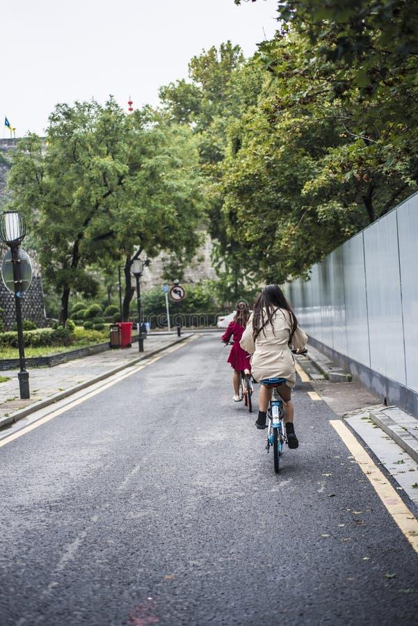 Due ragazze che guidano le biciclette senza fretta lungo il muro di cinta antico fotografie stock libere da diritti