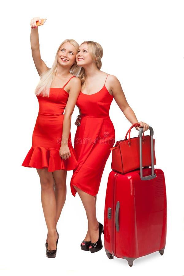 Due ragazze che indossano il rosso si veste con la grande fabbricazione della borsa e della valigia immagine stock