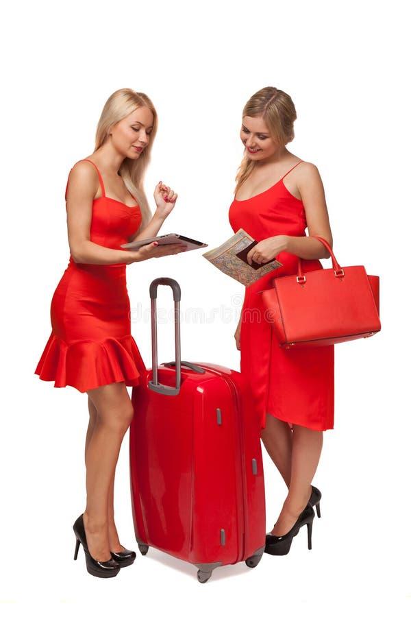 Due ragazze che indossano il rosso si veste con la grandi valigia e borsa e tabl fotografia stock libera da diritti